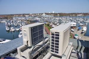 Splitgeräte auf dem Hoteldach während der Montage – im Hintergrund liegt der Yachthafen.
