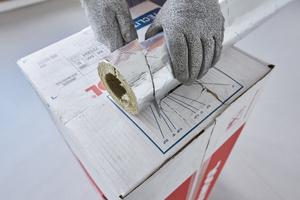 """<div class=""""bildtitel"""">Eine auf den Transportkartonagen aufgedruckte Schablone erleichtert den Zuschnitt der Rohrschale zur Isolierung von Leitungsbögen im benötigten Winkelmaß.</div>"""