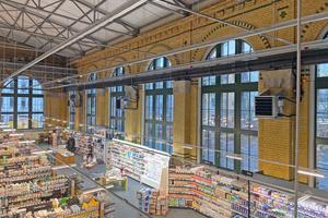 """<div class=""""bildtitel"""">Der hallenähnliche Charakter des Biomarkts wird durch die hohen Fenster und die Deckenkonstruktion betont.</div>"""