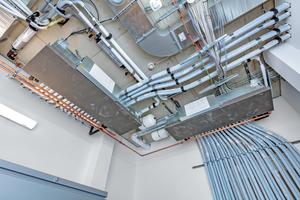 """<div class=""""bildtitel"""">Die HBC-Controller übernehmen den Wärmeaustausch zwischen den kältemittelgeführten Außenkreisläufen und den wasserbasierten Innenkreisläufen. Alle Rohrleitungen, die durch das Gebäude führen, sind mit Wasser befüllt.</div>"""