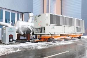 Luftgekühlter acr-Mietflüssigkeitskühler mit einer Kälteleistung von 1600 kW / je Einheit und das dazugehörige Pumpenmodul mit einer Förderleistung von 230 m³/h. Im Hintergrund eine hydraulische Weiche mit einem Volumen von 15000 Liter