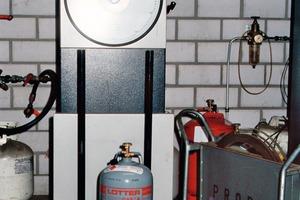 Blick in die Abfüllanlage eines Gaslieferanten. Beim Füllen stehen die Flaschen auf einer Waage [3]<br />