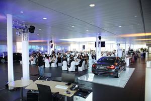 """<div class=""""bildtext"""">Die Gäste im großen Show-Room der BMW Niederlassung Stuttgart</div>"""